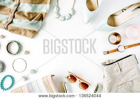 flat lay feminini clothes and accessories collage with cardigan trousers sunglasses watch bracelet high heel shoes earrings and purse on white background.