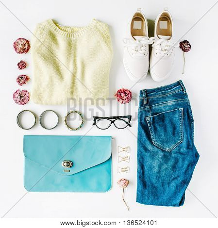 flat lay feminini clothes and accessories collage with cardigan jeans glasses bracelet clutch shoes and dry roses on white background.