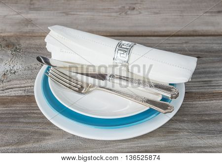 Beautiful table setting with white and blue plates linen napkin and silver fork and knife on an old wooden table