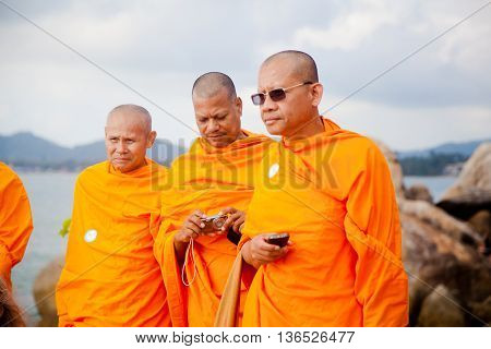 Koh Samui, Thailand - December 17 : three adult monk tourist wearing glasses and a orange dress with a camera and a phone in Thailand on Koh Samui in the feast of St. Anthony on December 17, 2012.