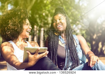 Afro friends using Tablet Computer in the park
