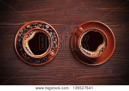 Top view on two cup of hot coffee and beans on a brown wooden background