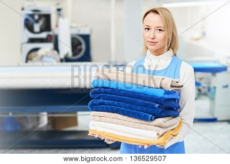 Portrait of a girl Laundry worker holding a clean towel to dry