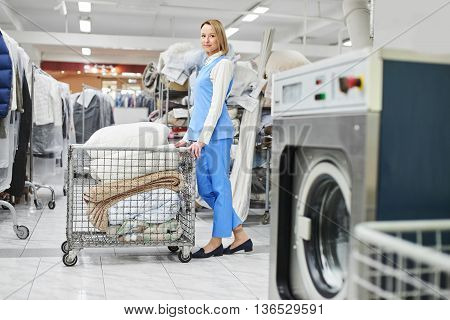 Girl Laundry worker rolls a cart with clean stuff at the dry cleaners