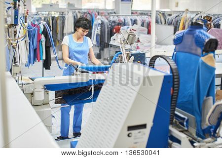 Worker Laundry irons iron clothes at the dry cleaners