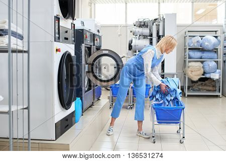 Female worker loads the Laundry clothing into the washing machine at the dry cleaners