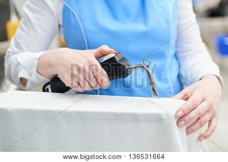 Hand Laundry worker in the process of removing stains by using a special dry-cleaning