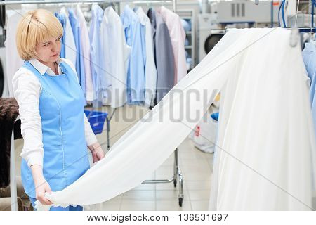 Girl worker Laundry looks and checks of white, sheer tulle at the dry cleaners