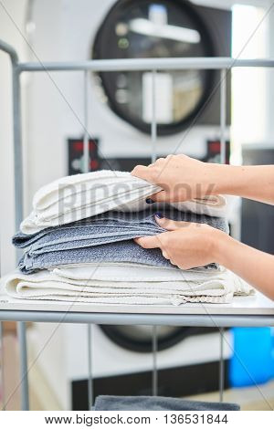 Female hands take a clean towel from the shelf at the dry cleaners