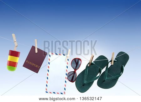 Summer items hanging on a washing line including passport flip flops sunglasses frozen lolly and international mailing envelope