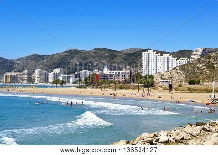 CULLERA, SPAIN - JUNE 23: Sunbathers at Raco Beach on June 23, 2016 in Cullera, Spain, with the the San Antonio Beach, the main beach in this popular tourist village, in the background