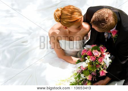 wedding couple hugging, the bride holding a bouquet of flowers in her hand, the groom embracing her
