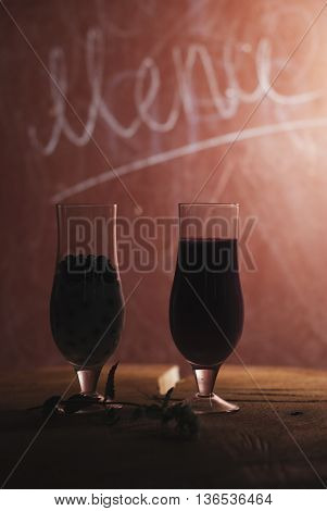 milkshake blueberry the silhouette of two glasses on a wooden table a berry smoothie and the inscription Menu
