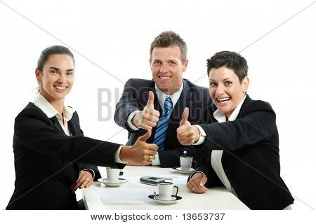 Happy business team having a meeting at coffee table, showing OK with thumbs up. Isolated on white.