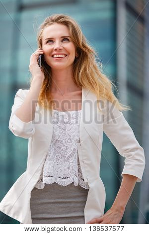 Young businesswoman talking on cellphone while walking outdoor. City business concept.