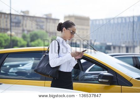 Young beautiful business woman with phone on a background of yellow taxis in the city center