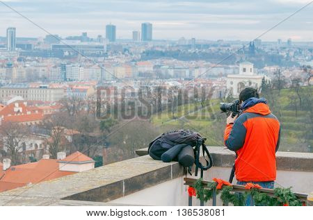 Photographer taking pictures of Prague from the hill.