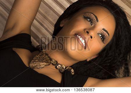 Beautiful smiling black woman with animal print eye shadow is lying.