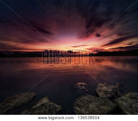 beautiful sunset over the lake with drammatic clouds