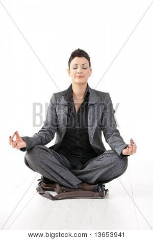 Young businesswoman sitting in yoga lotus position on her laptop case, meditating with closed eyes, isolated.?