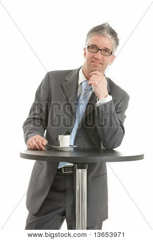 Businessman standing at coffee table, leaning on hand, thinking. Isolated on white.?