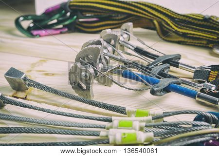 Equipment for mountaineering and rock climbing. On a wooden surface, pine boards. Slings with carbines, set stoppers and friends