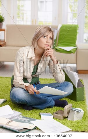 Worried woman thinking with paper in hand sitting on living room floor, checking documents,looking up, thinking.?