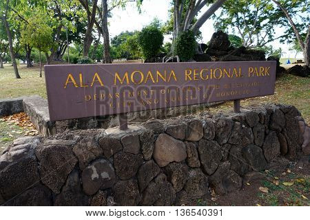 HONOLULU - FEBRUARY 21: Ala Moana Regional Park - Sign on top of lava rocks leading into park on February 21 2016 in Honolulu Hawaii. This 100-acre park has a wide gold-sand beach that is over a half-mile long.
