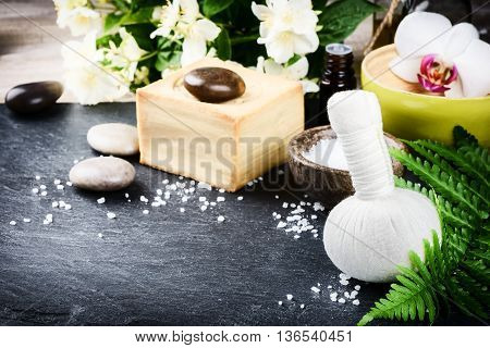 Spa setting with herbal massage ball flowers and essential oil. Wellness concept
