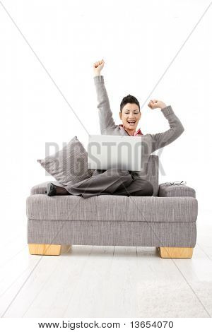 Happy businesswoman sitting on sofa with laptop computer. Celebrating business succes with hands raised, smiling.?
