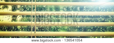 View of wet window with rain drops through blinds. Banner concept