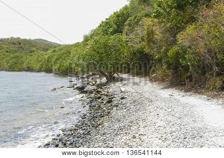 The shoreline showing water and rocky beach on St. John island in the Caribbean.