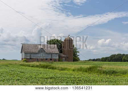 An old barn and silo in a field.