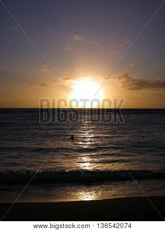 Dramatic Sunset through the clouds and reflecting on the Pacific ocean on the water lapping on the beach in Waikiki of Oahu Hawaii.