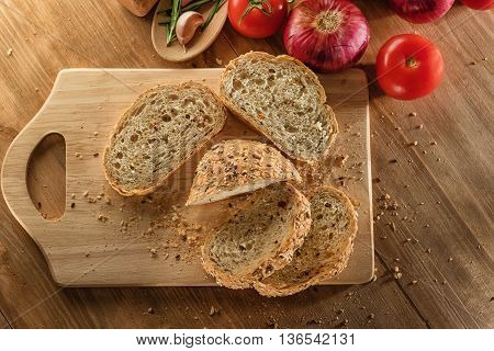 Whole Grain Bread on wooden board with tomatos