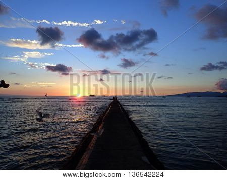 Rock Pier leads to Sunset over the Pacific ocean on the water with birds flying in the foreground and boats off the coast of Oahu Hawaii with Waianae Mountain range visible. February 2016.