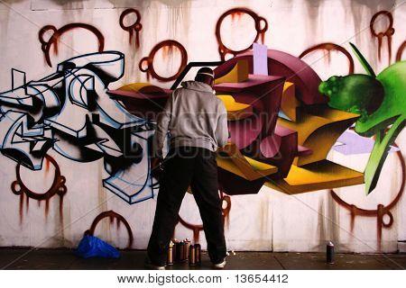 Unidentified man sprays graffiti on a wall like a vandal