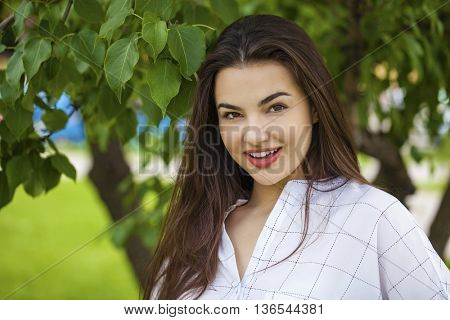 Close up portrait of beautiful young happy brunette woman with fresh and clean skin, summer street outdoors