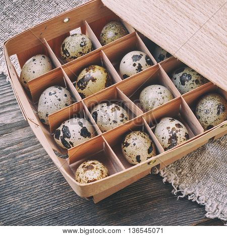 Quail eggs. The wooden packing box. The table covered with a rough cloth.