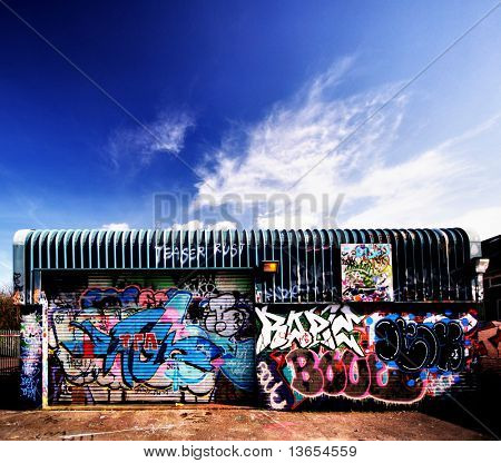 A building covered in Graffiti and a beautiful sky above