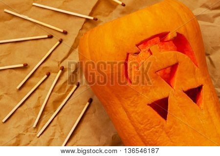 Carved smiling Scary Halloween pumpkin and matches, preparation for the holiday