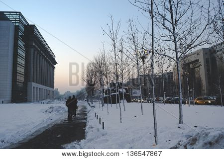 BUCHAREST, ROMANIA - January 22, 2016: People walking on Unirii Boulevard on a winter day between Bucharest Courthouse and the National Library building. BUCHAREST - January 22 2016