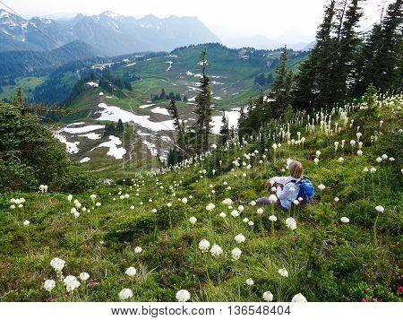 Woman sitting among flowers with mountain view. High Skyline trail on Mount Rainier National Park Seattle Washington USA.