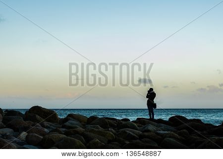 Happy woman on vacation photographing with a dslr camera on the beach