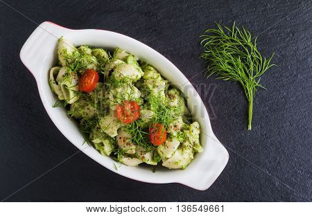 Broccoli pasta (shell shape) with dill and spices in baking dish on dark stone background. Top view.