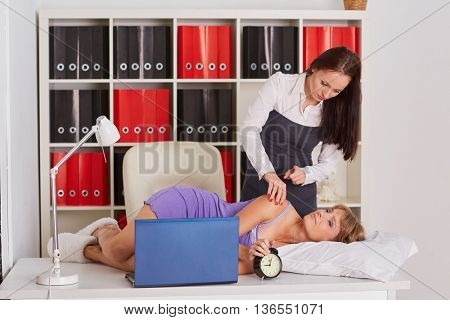 Young business woman tries to wake the sleeping coworker on a workplace in the office. Overworked.