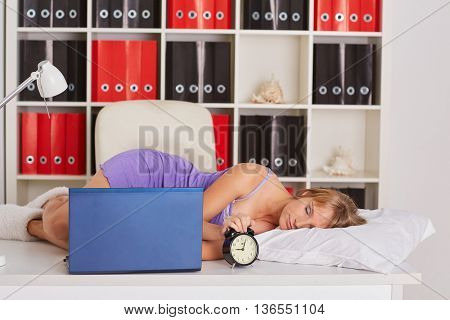 Tired young business woman is sleeping on workplace in the office.
