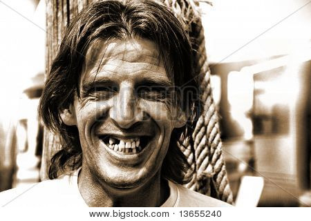 Grungey looking man in his 40's with some missing teeth but smiling happily