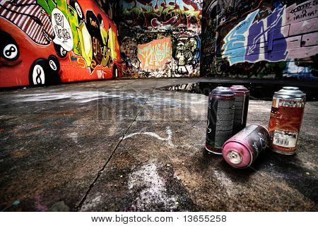 A derelict area of graffiti. Urban setting with empty spray cans neatly positioned to the right.