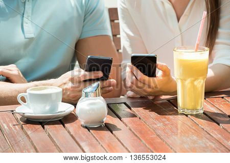 Close-up Of Young Happy Couple Sitting On Bench Using Mobile Phone